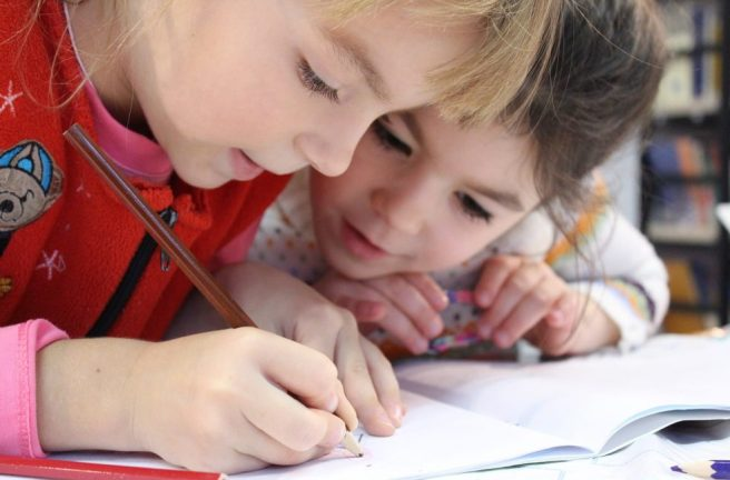 Two children collaborating on a piece of writing