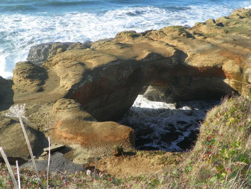 surf splashing into hollowed out rock formation