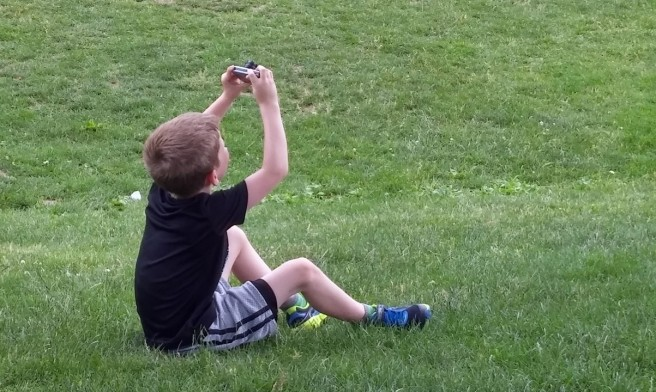 boy aiming camera toward sky