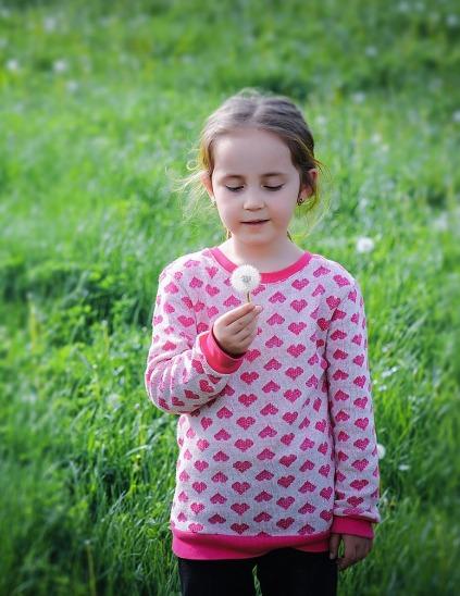 girl holding dandelion